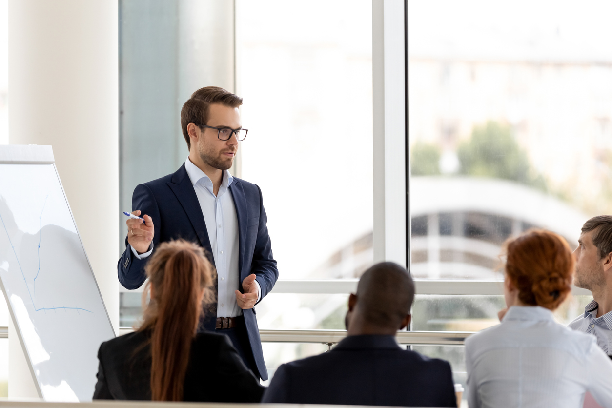 Man with glasses presents in front of group of people in office