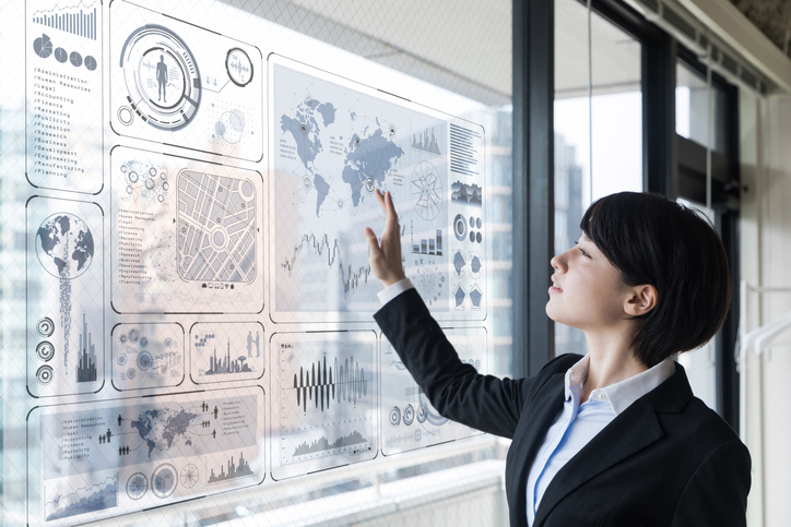 woman looks at window of maps and graphs